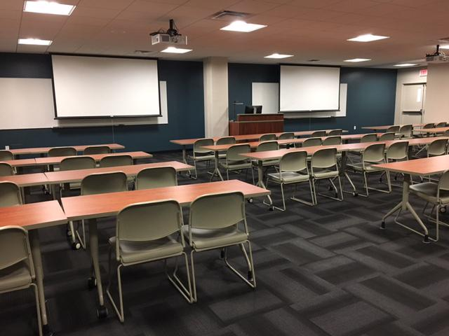 Penfield Classroom 215, showing its two projection screens, and four rows of tables with chair at them.