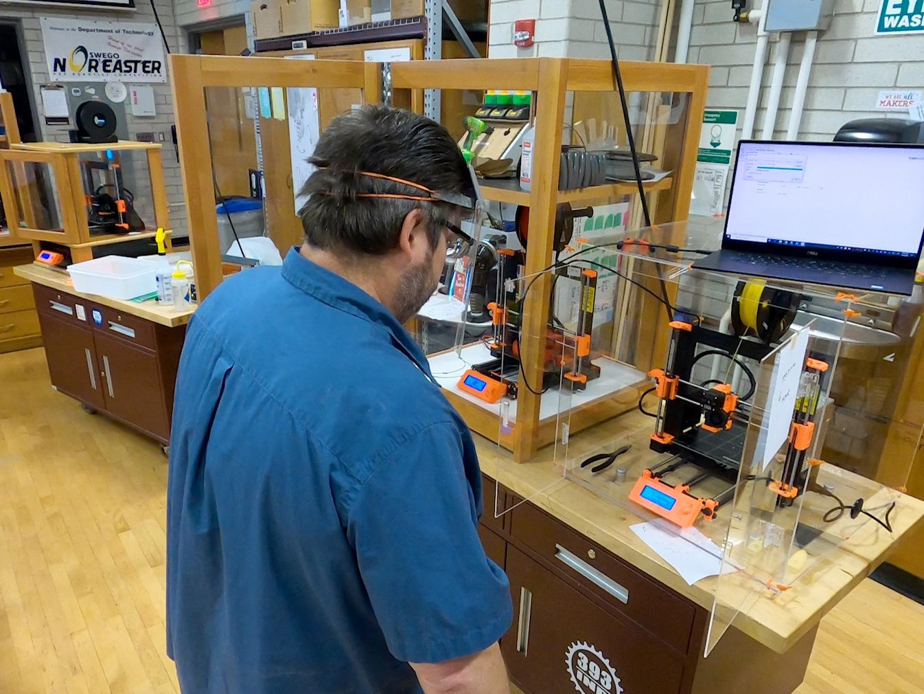 Dan Tryon manufactures face shields on a 3D printer in a Park Hall technology lab