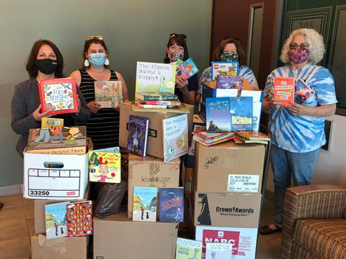 College participants and Oswego Bookmobile volunteers show off some of the hundreds of books donated to the local cause