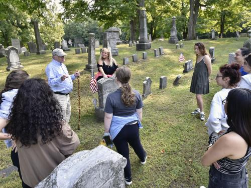 Oswego Town Historian (and 1966 SUNY Oswego alumnus) George DeMass speaks with theatre faculty member Jonel Langenfeld (center) and students from the college's storytelling class as they prepare for a family-friendly cemetery storytelling tour Oct. 29