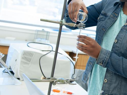 Student pouring in a chemistry lab