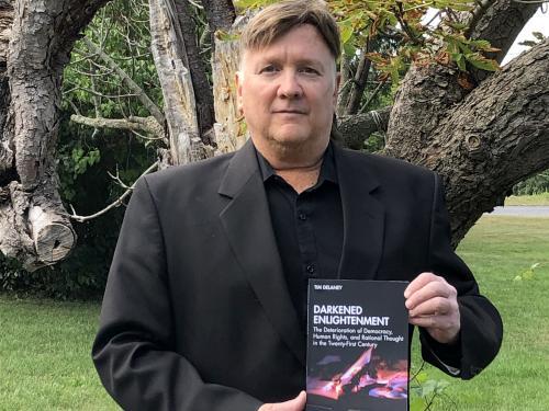 Tim Delaney holding new book, Darkened Enlightenment
