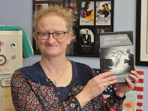 Helen Knowles with book Lights, Camera, Execution, a collaboration of three faculty members
