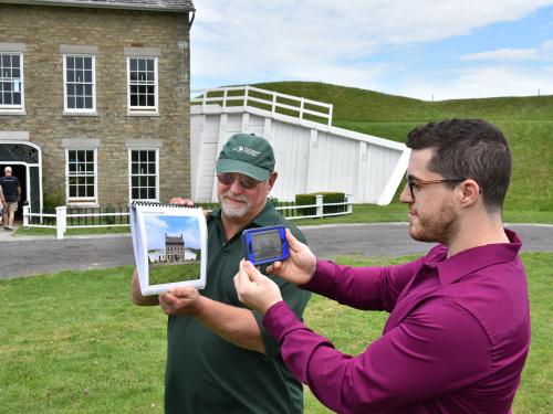 Fort Ontario's Paul Lear and SUNY Oswego graduate student Theo Johnson demonstrate an app that uses historical photos as reference points