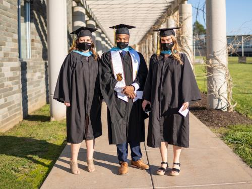 Three students outside Marano Campus Center for Commencement