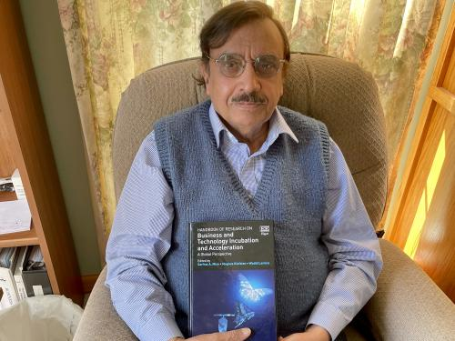 Sarfran Mian holds his most recent book, the first handbook for business incubation