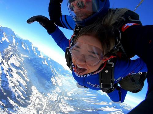 Student skydiving above the Alps, wearing look of exhilaration