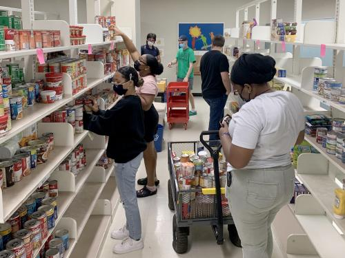 Student volunteers help stock shelves for the SHOP food pantry
