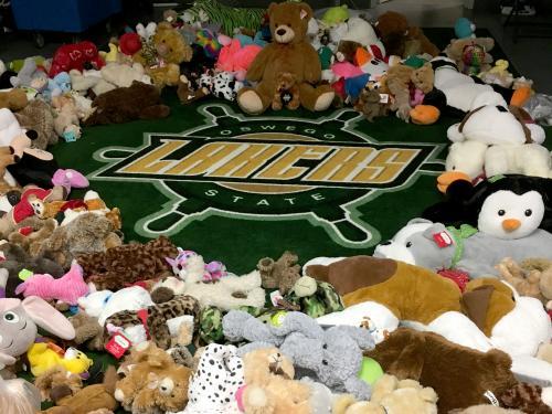 Stuffed animals ring a Lakers wheel logo in a hockey locker room