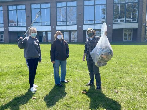 Three students show off some of what they've cleaned up as part of a campus effort