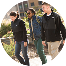 Three students walk across campus