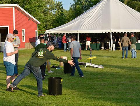 Alumnus throwing a frisbee during Reunion games