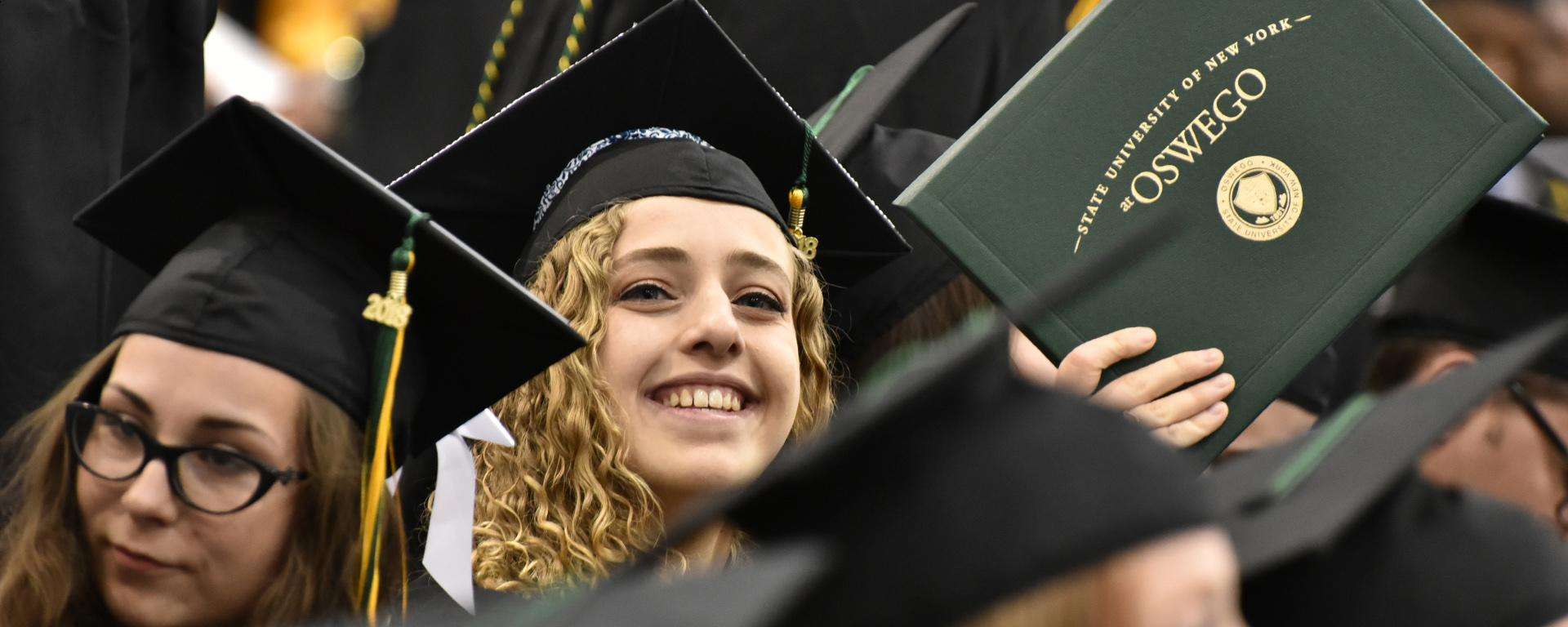 Student holds up diploma cover at Commencement