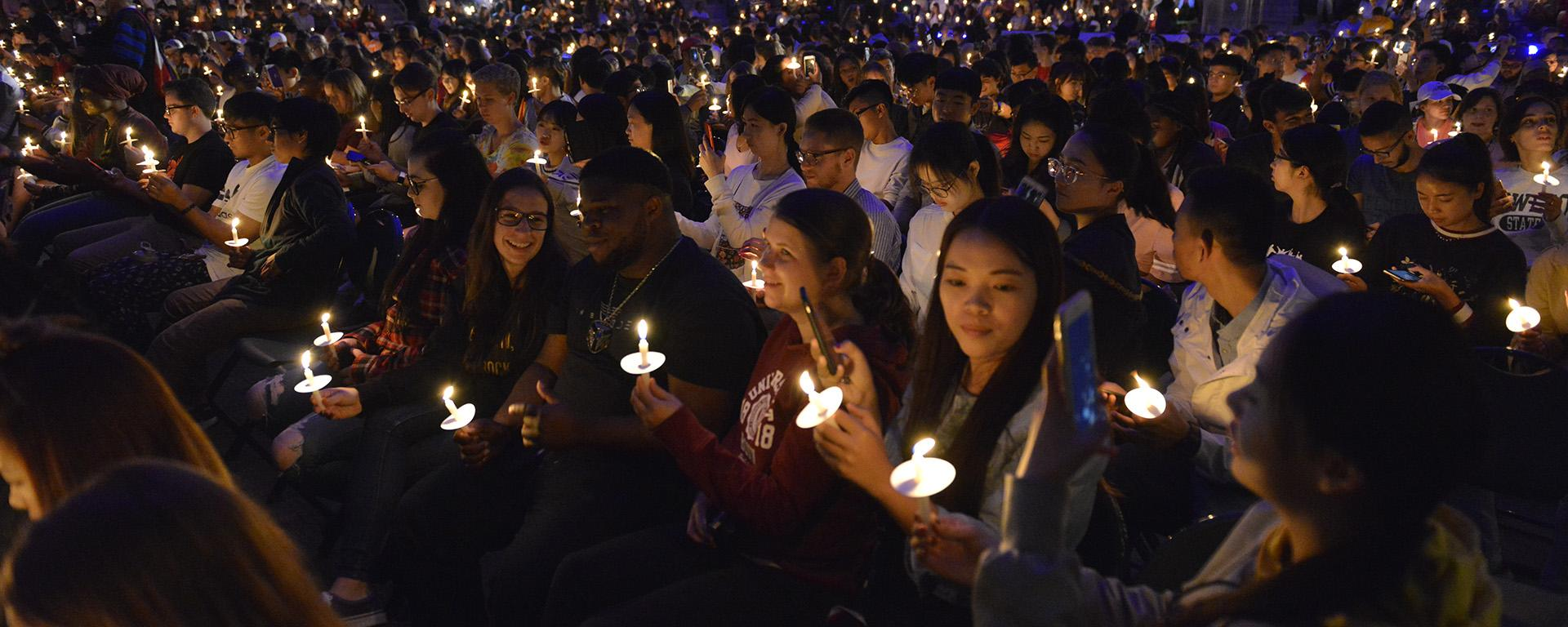 Students hold up candles during Torchlight