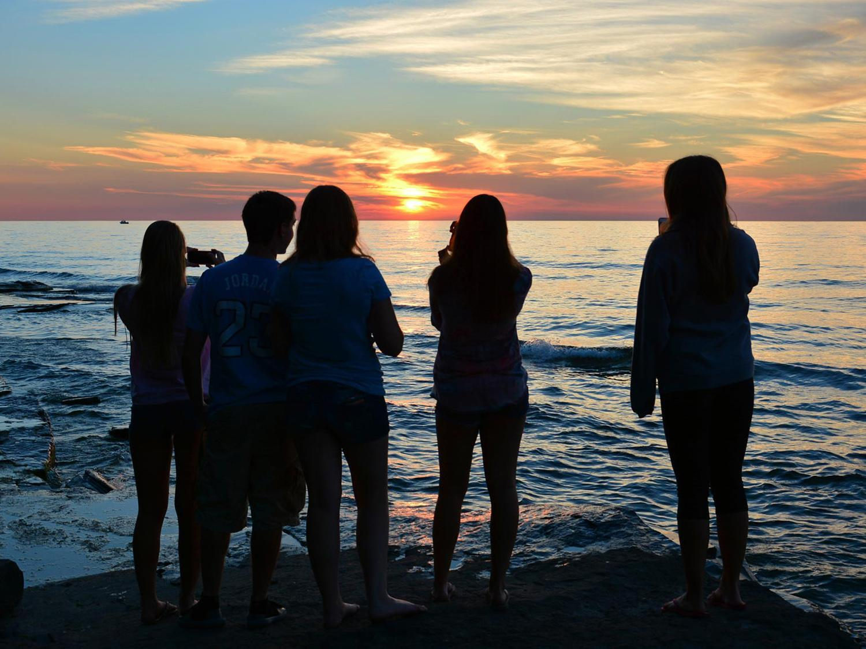Students standing near lake watching sunset
