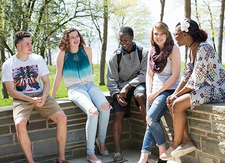 5 students sitting on a wall